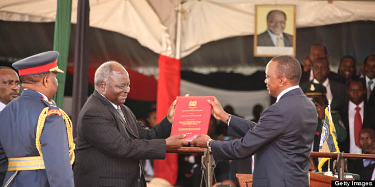 NAIROBI, KENYA - APRIL 9: (KENYA, UGANDA, RWANDA and TANZANIA OUT) Outgoing President Kibaki hands over the Constitution of Kenya to President Uhuru Kenyatta after he was sworn in as Kenyan's 4th President on April 9, 2013 in Nairobi, Kenya. Kenyatta received masses of support from the citizens of Kenya despite being under investigation for crimes against humanity. (Photo by William Oeri/ Nation Media/Gallo Images/Getty Images)
